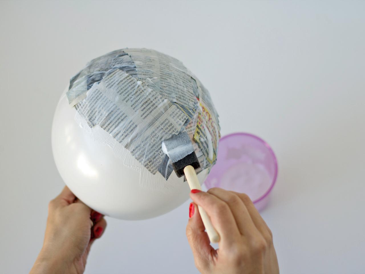 paper mache balloon with newspaper and paint brush