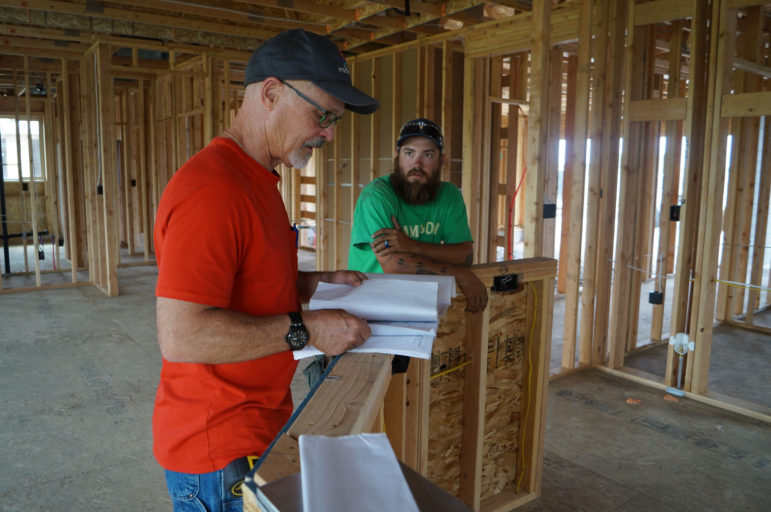 Building inspector Robert Trumbull meets with a construction worker at an Aho home on East Junco Str