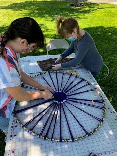 two girls weaving fabric on a hula hoop frame
