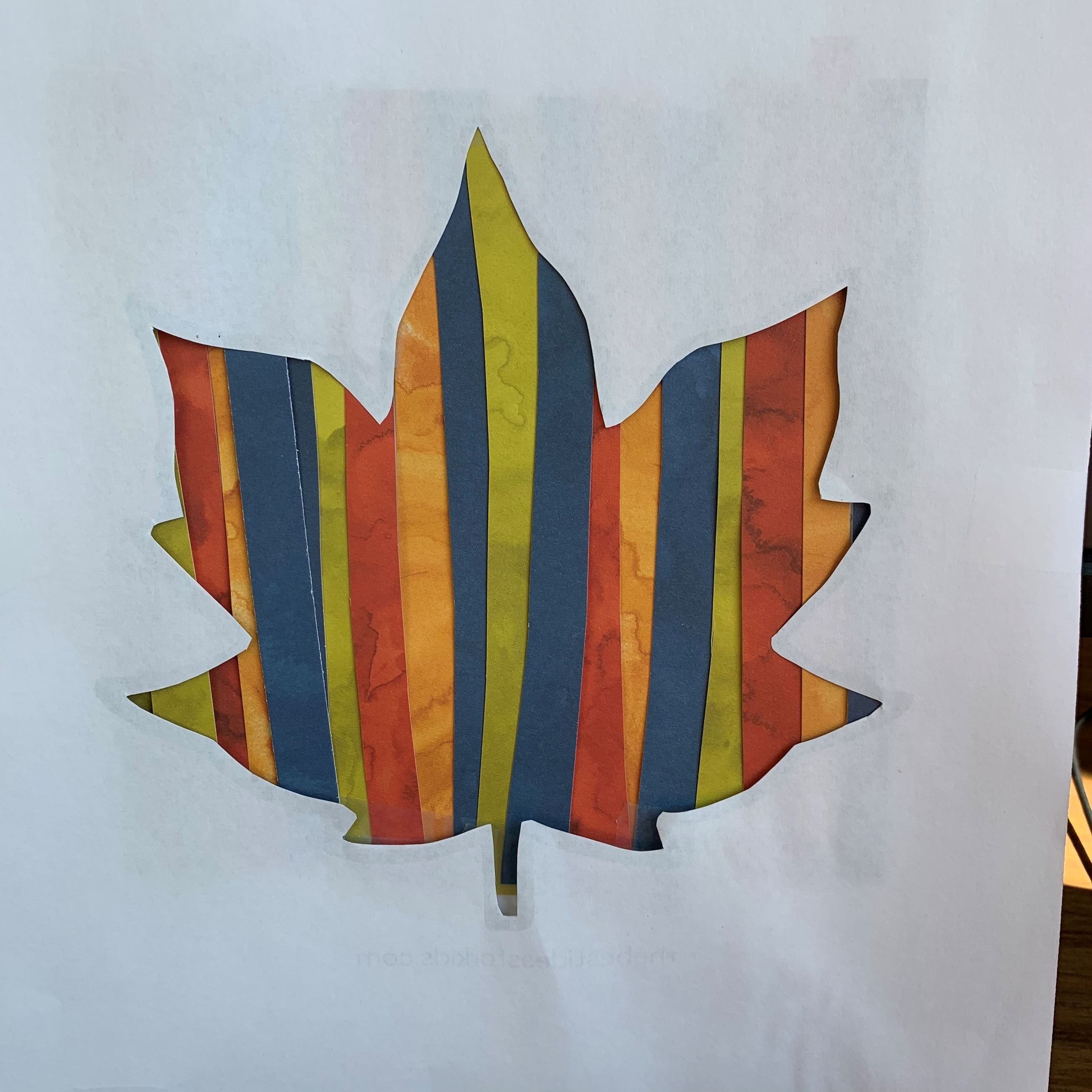 cut out of maple leaf with red, green, blue, and orange strips of paper