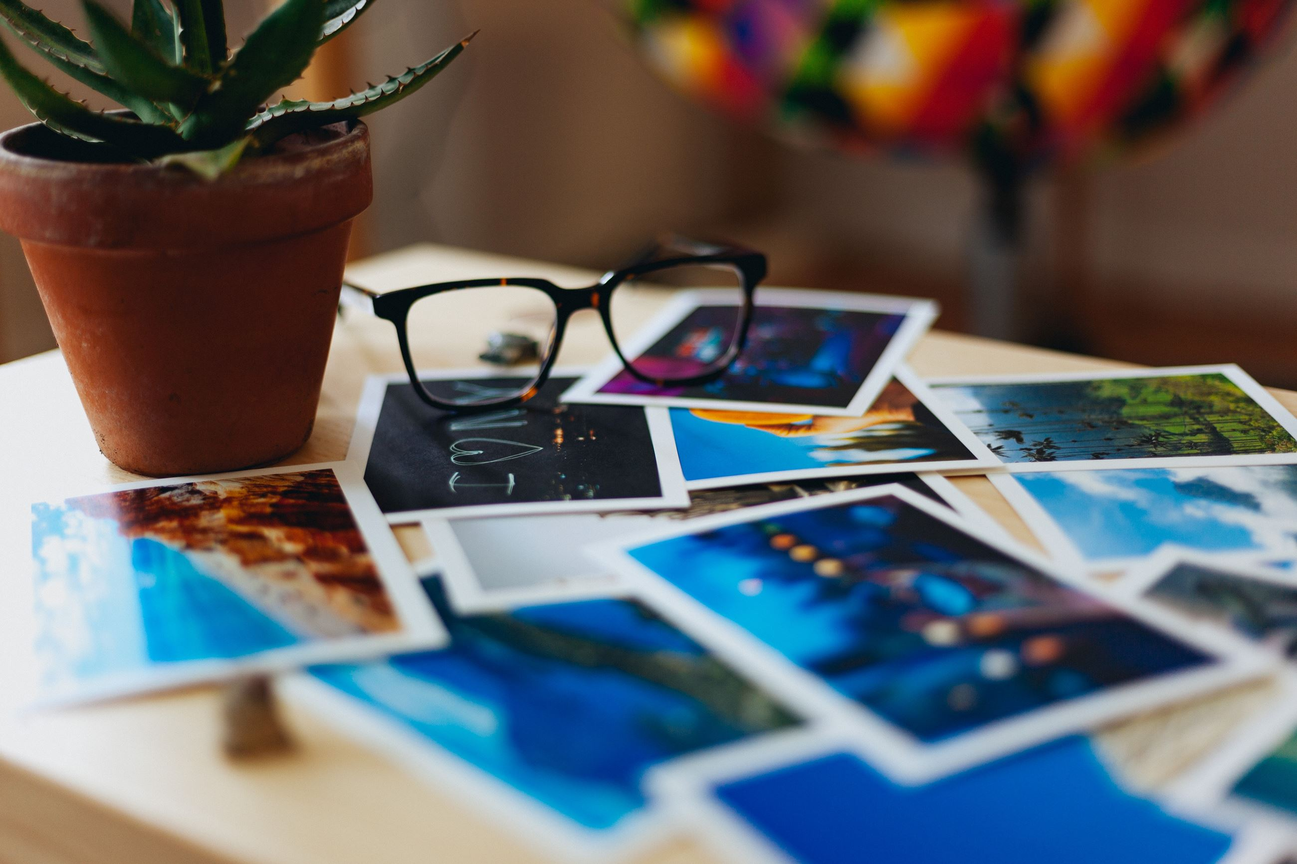 A photograph displaying postcards and a pair of glasses on a table