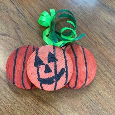a repurposed wooden token painted to look like a pumpkin